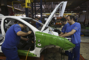 Iranian car workers assemble a car at the state-run Iran-Khodro automobile manufacturing plant near Tehran, Iran, Sunday, June 29, 2014. Iran began exporting automobiles to Russia for the first time in five years on Sunday, after meeting upgraded emission standards, the country's largest auto manufacturer said. (AP Photo/Vahid Salemi)