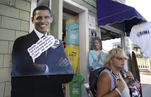 A passer-by, right, departs a store that features cut-outs of President Barack Obama, left, and First Lady Michelle Obama, center, Saturday, Aug. 9, 2014, in Oak Bluffs, Mass., on the island of Martha's Vineyard. President Obama and his family are returning to the island off the Massachusetts mainland Saturday. The president is doing something unusual with his summer vacation on Martha's Vineyard: He'll come back to Washington midway through the getaway to attend White House meetings. (AP Photo/Steven Senne)