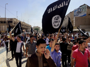 """FILE - In this Monday, June 16, 2014 file photo, demonstrators chant pro-Islamic State group slogans as they wave the group's flags in front of the provincial government headquarters in Mosul, 225 miles (360 kilometers) northwest of Baghdad, Iraq. The IS declaration of a """"caliphate"""" in Iraq and Syria inspired a stream of thousands of foreign fighters to join it and earned it pledges of allegiance by individual militants around the region. (AP Photo, File)"""