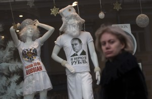 A woman walks past a shop window with a T-shirt on display reading, 'I Believe in the Ruble', in downtown Moscow, Russia, on Monday, Dec. 22, 2014. The ruble has been the worst performing currency this year along with the Ukrainian hryvnia, having lost half of its value. Its collapse in the past weeks sparked a consumer boom as worried Russians flocked to the shops to buy cars and durable goods before prices rose further. (AP Photo/Pavel Golovkin)