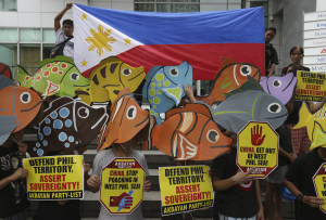 Protesters wearing fish-shaped hats gather outside the Chinese Consulate during a rally in suburban Makati, south of Manila, Philippines on Tuesday June 11, 2013. The group held the rally to oppose China's alleged continued intrusion and poaching activities in the West Philippine Sea. (AP Photo/Aaron Favila)