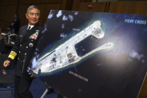 "In this Sept. 17, 2015, file photo, Adm. Harry B. Harris, Jr., U.S. Navy Commander, U.S. Pacific Command walks past a photograph showing an island that China is building on the Fiery Cross Reef in the South China Sea, as the prepares to testify on Capitol Hill in Washington before the Senate Armed Services Committee hearing on maritime security strategy in the Asia-Pacific region. The U.S. Navy's challenge to China's sovereignty claims in the South China Sea was not designed as a military threat, Harris said Tuesday, Nov. 3, 2015, in a mostly upbeat speech about prospects for preventing U.S.-China disputes from escalating to conflict. Speaking in the Chinese capital, Harris cited a recent statement by U.S. Defense Secretary Ash Carter that the international order ""faces challenges from Russia and, in a different way, from China, with its ambiguous maritime claims,"" including Beijing's claim to nearly all of the South China Sea. (AP Photo/Cliff Owen, File)"