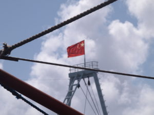 Flag atop a Chinese Coast Guard vessel near Panatag/Scarborough Shoal in the South China Sea. As seen from a Philippine fishing boat on Philippine Independence Day. June 12, 2016. (Photo credit: Anders Corr and Kalayaan Atin Ito.)