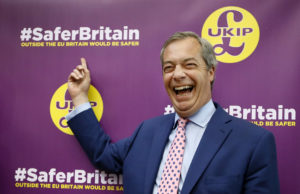 Nigel Farage, leader of Britain's UK Independence Party laughs as he points to a UKIP poster, before delivering a speech on the forthcoming EU referendum, in London, Friday, April 29, 2016. (AP Photo/Kirsty Wigglesworth)
